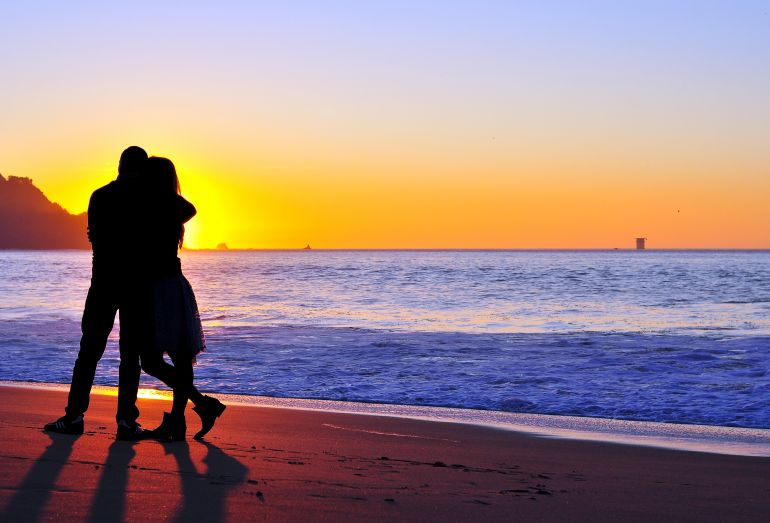 Silhouette of happy family who playing on the beach at the sunset time. Lifestyle