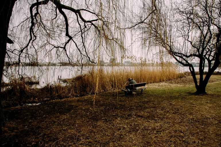 Lonely man sits on bench in park