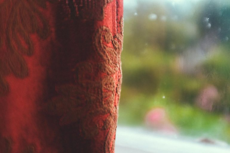 Old red curtain and blurry window
