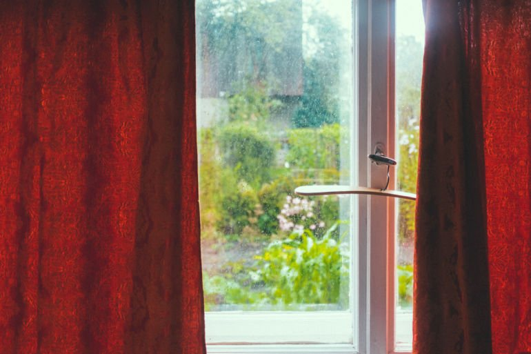 Window with red curtains in old summerhouse