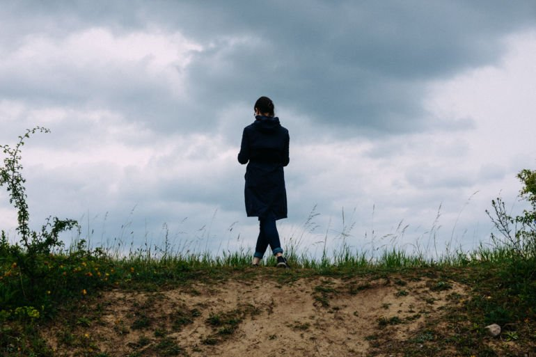girl standing against sky in a field