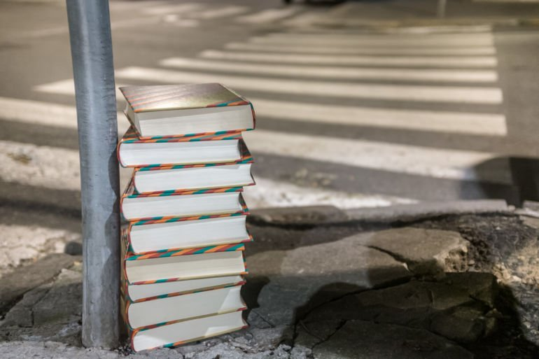 Stack of books on asphalt in the city