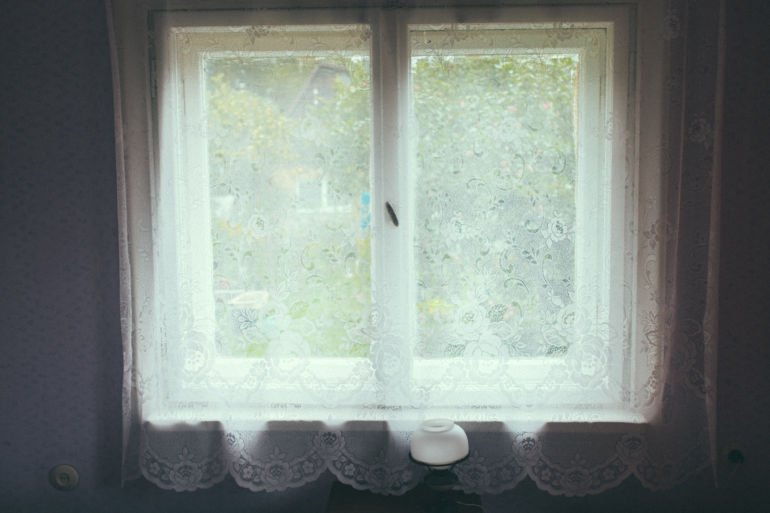 Old curtains and window at dacha