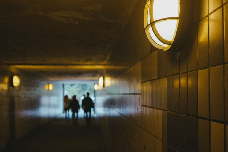 The silhouettes of people walking through the tunnel