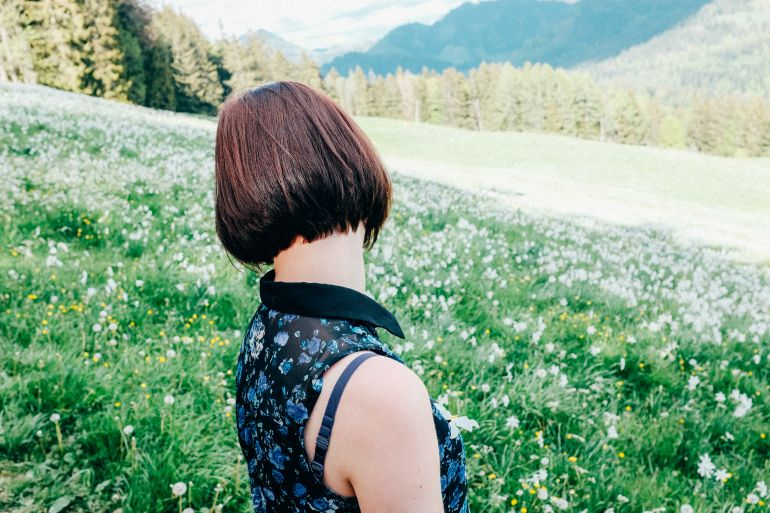 Young woman in a field of flowers in the Alps