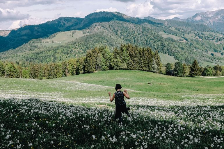 Young woman walks in flower field in the Alps