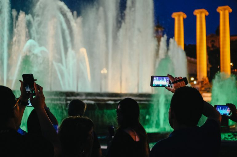 Tourists photograph the magic fountains in Barcelona