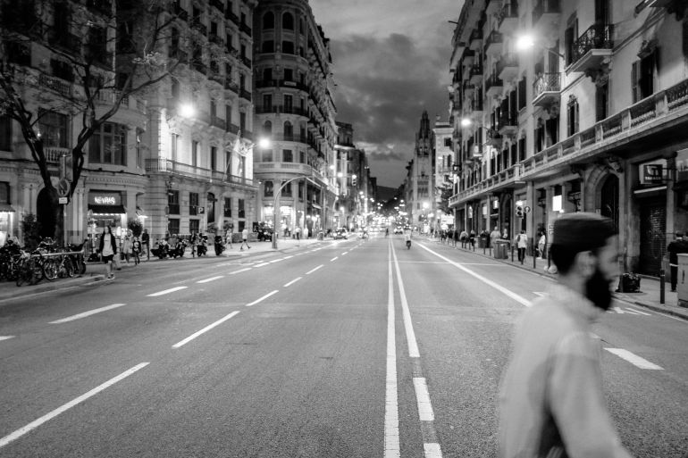 A man crosses the road in Barcelona at night