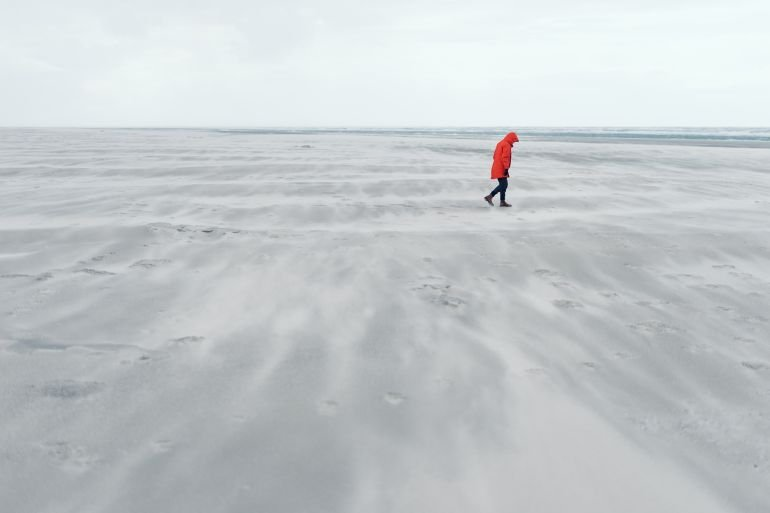Person in red jacket on the North Sea coast