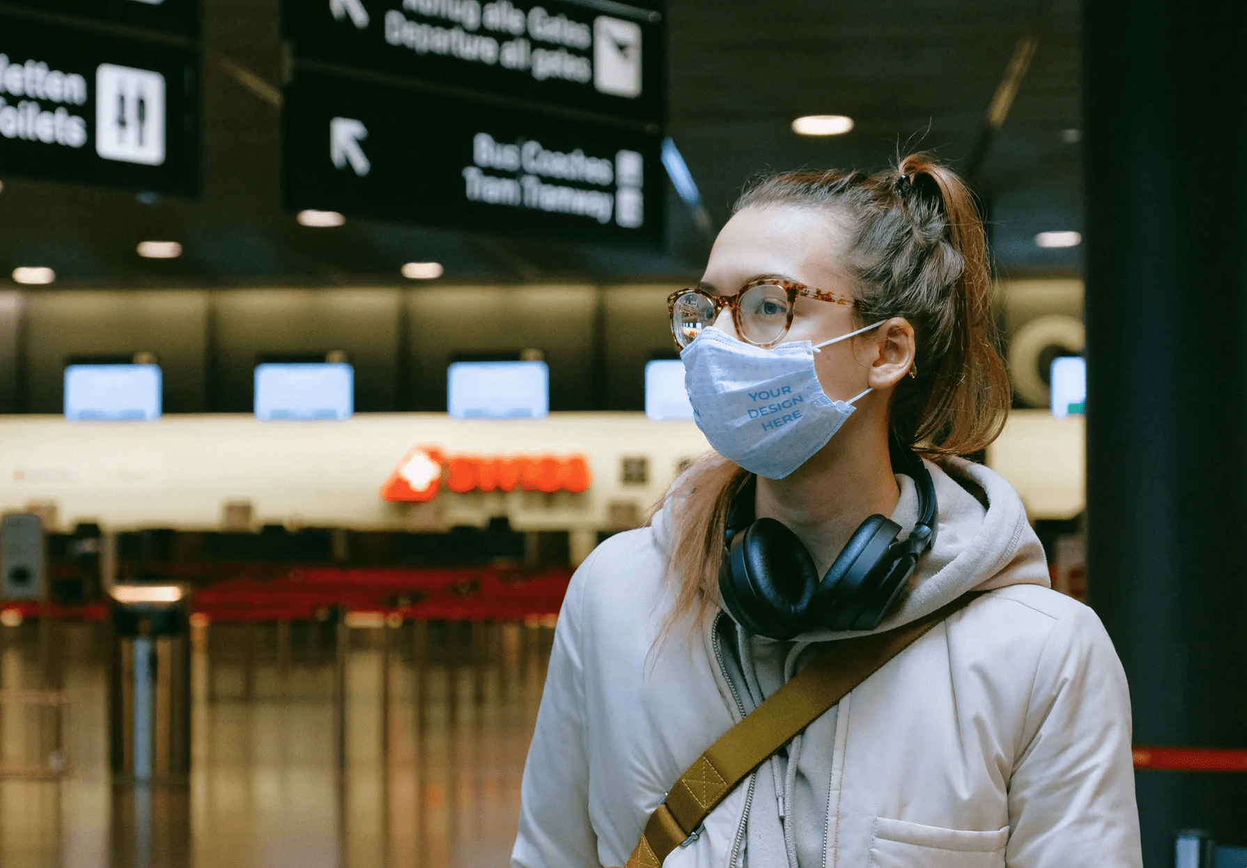 Woman Wearing a Face Mask at the Airport [Free Mockup Generator]